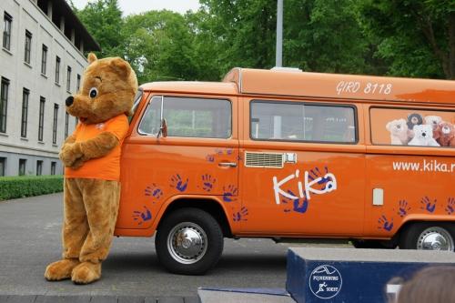 KiKa beer leunt tegen oranje KiKa VW Volkswagen bus